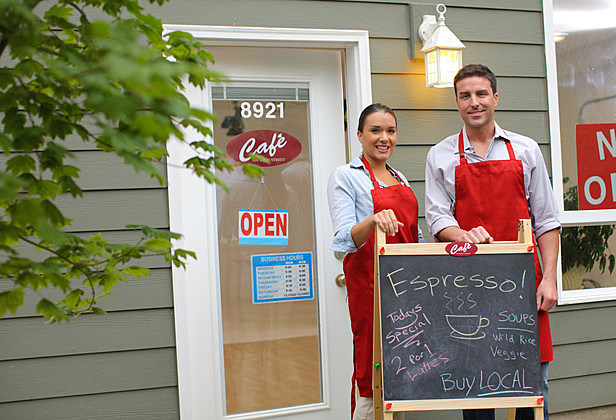 Small business owners standing in front of cafe