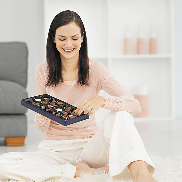 Front view of a woman sitting on the ground, enjoying a box of chocolates