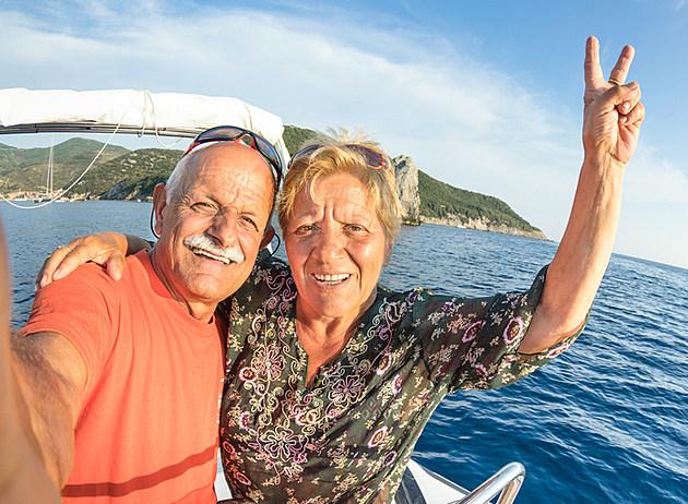 Adventurous senior couple taking travel selfie at Giglio Island