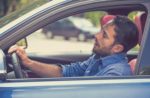 sleepy tired fatigued man driving car in traffic